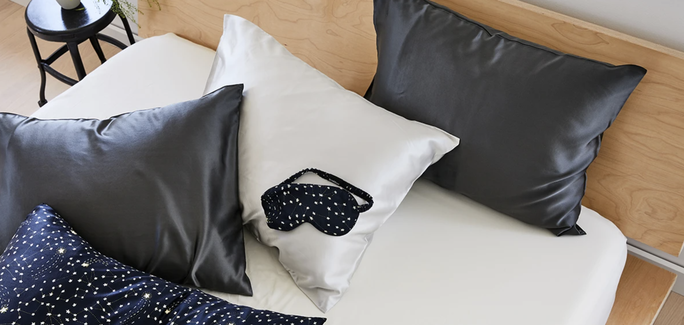 close up of brooklinen sheets in different colors on pillows in bed