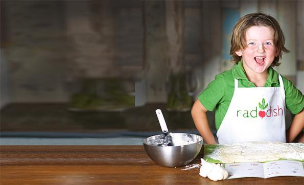 Child wears apron in front of food preperation station