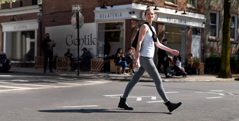 woman walking across the street in workout gear