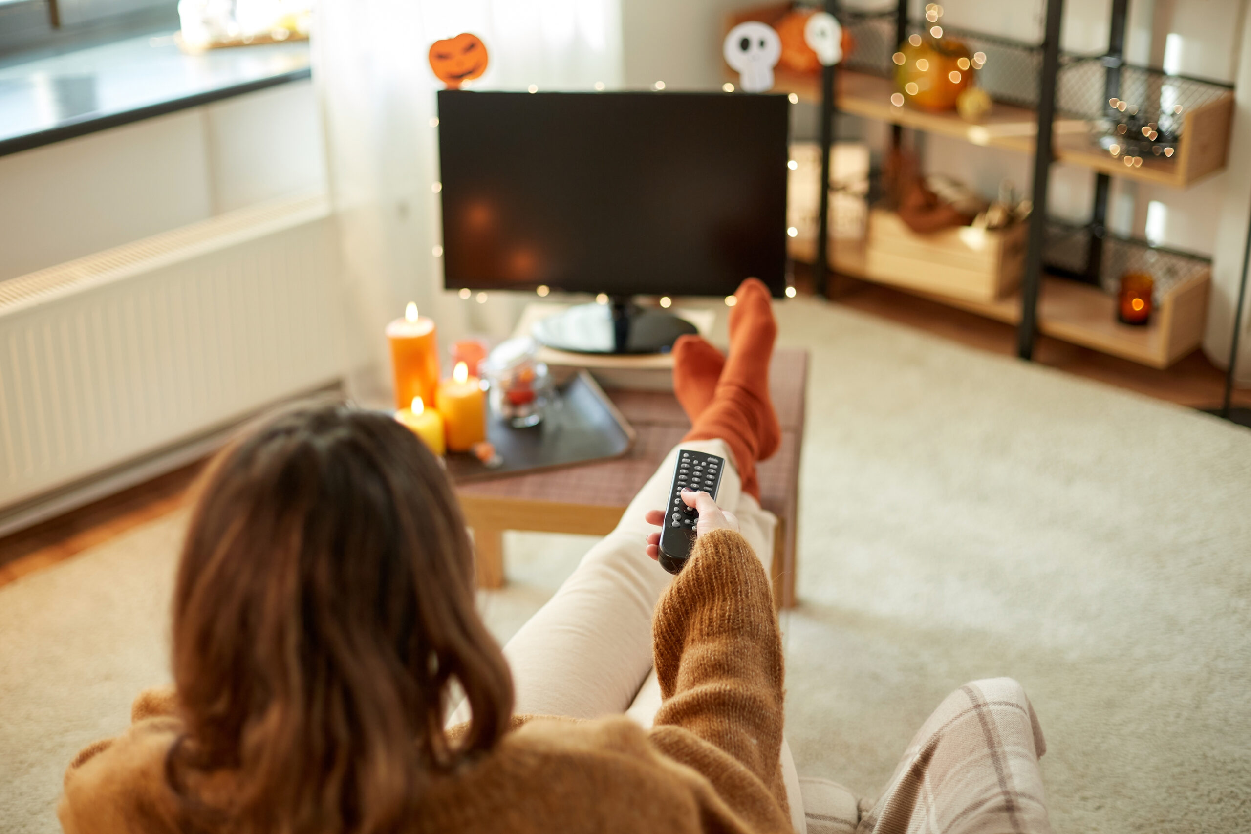 woman getting ready to watch tv with Halloween decorations